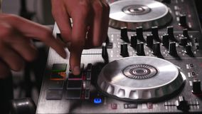 DJ mixes songs on equipment, hands closeup stock video