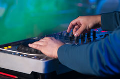 Dj mixes the track in the nightclub at a party. Dj playing the track in the nightclub at a party Stock Photos