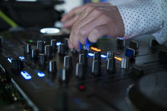 Dj mixes the track in nightclub at party with dancing people on blur background Royalty Free Stock Image