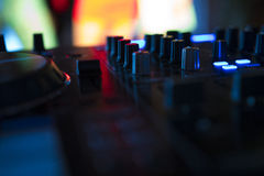 Dj mixes the track in nightclub at party with dancing people on blur background Stock Images