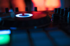 Dj mixes the track in nightclub at party with dancing people on blur background. Dj mixes with dancing people Royalty Free Stock Image