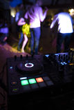 Dj mixes the track in nightclub at party with dancing people on blur background Stock Image