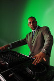 DJ mixing music. DJ wearing a suit mixing some music. Green background Royalty Free Stock Photo