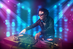 Dj mixing music in a club with blue and purple lights Royalty Free Stock Photos