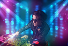 Dj mixing music in a club with blue and purple lights Royalty Free Stock Image