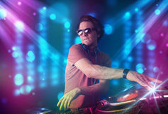 Dj mixing music in a club with blue and purple lights Stock Images