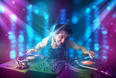 Dj mixing music in a club with blue and purple lights Stock Photography