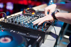 DJ mixing music on console Royalty Free Stock Image