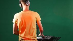 The dj mixing music standing at his deck, dance in his earphone, from the back stock photo