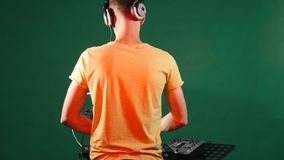 The dj mixing music standing at his deck, dance in his earphone, from the back stock footage