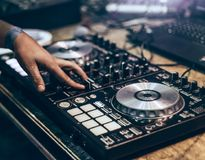 Dj mixing music track by hand on turn table.  royalty free stock photography