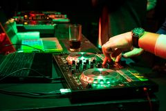 DJ music console and laptops in bright colors of light royalty free stock images