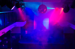 DJ in Night Club Lit with Colorful Lights Royalty Free Stock Photography