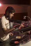 A DJ in a nightclub at his mixing desk Stock Photo