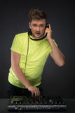 DJ no trabalho isolado no fundo cinzento escuro Fotografia de Stock