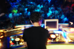 DJ performing in the club. With crowd in the background Stock Photo