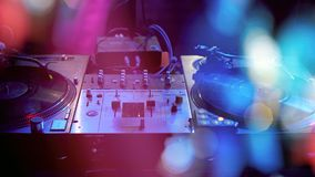 DJ performs in a nightclub at a party. Beautiful blurry colored bokeh from the lights of searchlights and illuminators Royalty Free Stock Photos