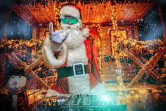 Dj playing at christmas. DJ Santa Claus in luminous glasses and headphones holds a party near his house decorated with lights. Christmas songs and music stock photo
