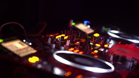 Dj playing dance music on night party. Close up of hands of dj playing dance music on party. Modern cd usb player in disco club and strobe light are visible