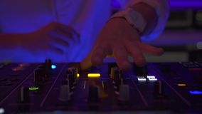 Dj playing dance music on sound console at event party in nightclub. DJ mixer player and mixing music console for dance. Party. Disc jockey panel and mixing stock footage