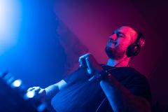 DJ playing house and techno music in a night club. Mixing and controlling the music royalty free stock photo
