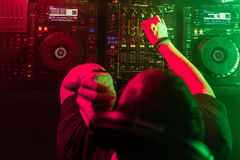 DJ Playing House and Techno music in a night club. Mixing and Controlling the Music royalty free stock photography