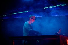 Dj playing mixing music at night party under blue and red lights. Fun, youth, entertainment and fest concept Royalty Free Stock Photography