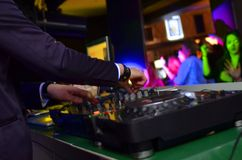 DJ playing music at the club. Blurred people on background Stock Images