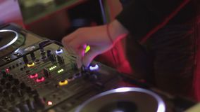 DJ playing music at mixing console, twisting controls on sound board, nightclub. Stock footage stock footage