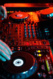 DJ playing music in night club party. Turntable equipment in dar. K red. Nightlife concept. Vertical Royalty Free Stock Photo