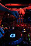 DJ playing music in night club party. Turntable equipment in dar. K red. Nightlife concept. Vertical, Blue lights Stock Image