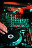 DJ playing music in night club party. Turntable equipment in dar. K red. Nightlife concept. Vertical, green lights Royalty Free Stock Images