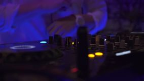 Dj playing music on sound console at dance event in night club party. DJ mixer player and music console for disco party. Disc jockey panel and mixing deck with stock video footage