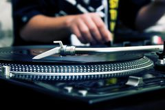 DJ playing music from vinyl record. Focus on the professional turntable with a DJ adjusting the volume on controller Royalty Free Stock Photos
