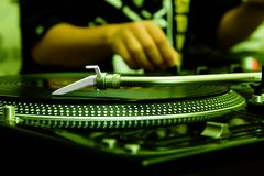 DJ playing music from vinyl record. Focus on the professional turntable with a DJ adjusting the volume on controller Stock Photo