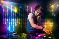 Dj playing songs in a disco with light show Royalty Free Stock Image