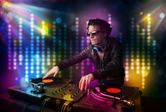 Dj playing songs in a disco with light show. Young Dj playing songs in a disco with light show Royalty Free Stock Photography