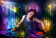 Dj playing songs in a disco with light show. Young Dj playing songs in a disco with light show royalty free stock image
