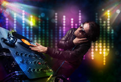 Dj playing songs in a disco with light show Royalty Free Stock Images