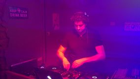 Dj plays in night club illuminated by colorful light.