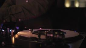 DJ plays vinyl turntables. In a nightclub - bar.