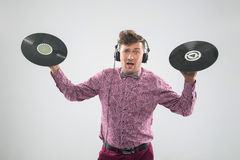 DJ posing with vinyl record. Half-length closeup portrait of excited young DJ with stylish haircut, bow tie and headphones posing with two vinyl records isolated stock image