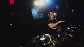 DJ que gira e que dança na plataforma giratória no partido no clube noturno iluminações clap video estoque