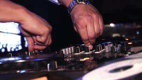 DJ que gira e que mistura na plataforma giratória no partido no clube noturno cheering equipamento celebration Música video estoque