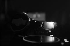 DJ que gira, misturando, e riscando em um clube noturno, nas mãos controles da trilha da emenda do DJ de vários na plataforma do  Fotos de Stock