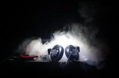 DJ que gira, misturando, e riscando em um clube noturno, nas mãos controles da trilha da emenda do DJ de vários na plataforma do  Fotos de Stock Royalty Free