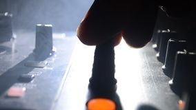 DJ que gira, misturando, e riscando em um clube noturno, nas mãos controles da trilha da emenda do DJ de vários na plataforma do  filme