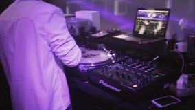 DJ que gira na plataforma giratória no partido no clube noturno cheering Portátil Mostra do laser filme