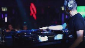 DJ que gira na plataforma giratória no partido no clube noturno Multidão de povos da dança vídeos de arquivo