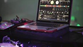 DJ que gira na plataforma giratória no partido no clube noturno Portátil Projectores roxos video estoque